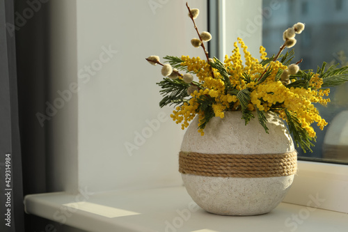 Obraz Beautiful mimosa flowers in vase on window sill indoors, space for text - fototapety do salonu