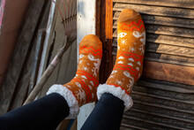 Feet With Orange Socks Supported By Rustic Wood Texturizad