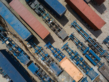 Top View Of Flatbed Semi Trailers And Containers For Rent Stored In An Empty Dirt Lot.