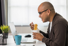 Young Asian Businessman Working With Laptop. Indian Freelancer Eating Instant Noodle While Working. He Work At Home. He Had To Hurry And Finish His Work.