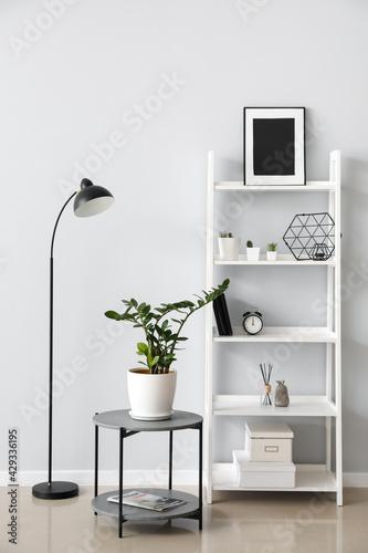 Interior of modern room with shelf unit and lamp - fototapety na wymiar