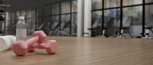 3D Rendering, Pink Dumbbells On Wooden Table With Sport Stuffs In Concept Fitness Room With Training Equipments In The Back