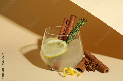 Fotografiet Glass of lemonade with cinnamon and rosemary on beige background