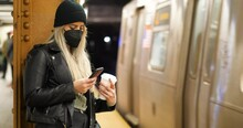 Woman Boarding Train Using Smartphone With A Mask On In The Subway Station In New York City