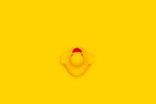 Un Pato De Goma Amarillo Sobre Un Fondo Amarillo Liso Y Aislado. Vista Superior. Copy Space