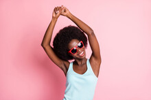 Portrait Of Optimistic Brunette Curly Lady Dance Look Empty Space Wear Spectacles Blue Top Isolated On Pastel Pink Color Background