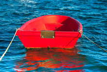 Red Dinghy .Isolated. Copy Space. Small Wooden  Bright Red Dingy Moored In Marina. Stock Image.