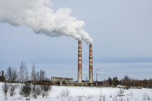 Industrial Smoke From A Chimney On A Cloudy Blue Sky Background. Ecological Pollution