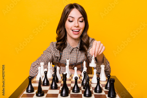 Photo Photo of impressed nice brunette lady sit play chess wear shirt isolated on vivi