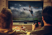 Men With Betting Application In Phone. Group Of Friends Watching TV, Sport Match Together. Emotional Fans Cheering For Favourite Team, Watching On Exciting Game.