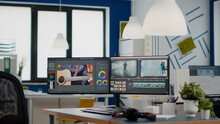 Empty Modern Creative Agency Office With Dual Monitors Setup With Processing Video Film Montage. Video Editing Start Up Studio Company With No People In It And Post Production Software On Pc Displays