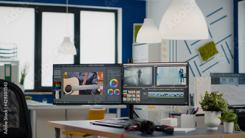 Obraz Empty modern creative agency office with dual monitors setup with processing video film montage. Video editing start up studio company with no people in it and post production software on pc displays - fototapety do salonu
