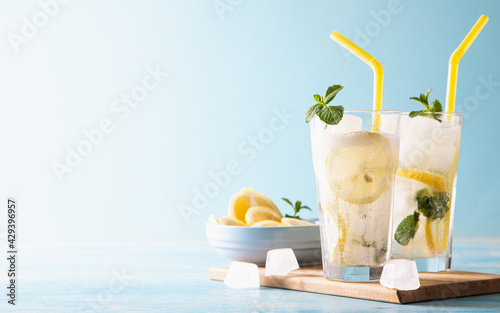 Obraz Two glass with lemonade or mojito cocktail with lemon and mint, cold refreshing drink or beverage with ice on blue background. Copy space - fototapety do salonu