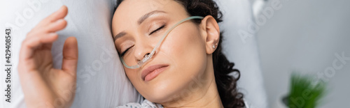 Obraz overhead view of ill african american woman with nasal cannula sleeping in hospital bed, banner - fototapety do salonu