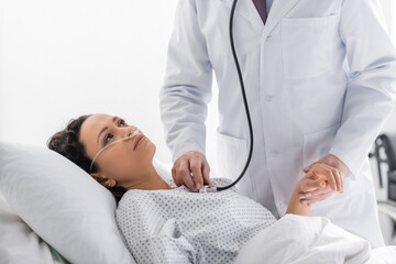 doctor holding hand of sick african american woman while examining her with stethoscope