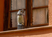 Owl-shaped Scarecrow On The Exterior Window Sill