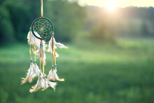 Magic Dream Catcher On Summer Landscape, Gentle Green Natural Background. Ethnic Ritual, Shaman Native Amulet. Hygge, Lagom, Relax Concept. Copy Space