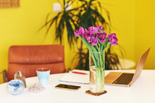 Colorful Workplace With Portable Laptop Computer, Mineral Crystals And Beautiful Spring Flowers