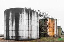 Old Fuel Oil Tanks With Fuel Oil Stains And Traces Of Rust At An Abandoned Industrial Plant