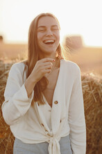 Portrait Of A Smiling Beautiful Girl With Long Hair In A Jeans Skirt. Woman Enjoying A Walk In A Wheat Field With Hay Bales On Summer Sunny Day.