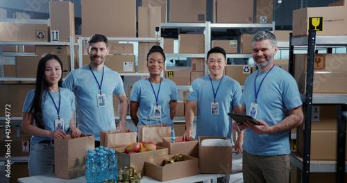 Wallpaper Mural Multi-race cooperative team of volunteer charity workers collecting food for poor people