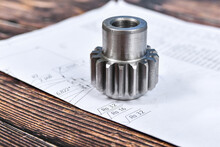 A Cogwheel Made On A Gear Cutting Machine Lies On The Technical Drawings.