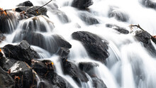 White Rushing Water Flowing Over Exposed Jagged Rocks