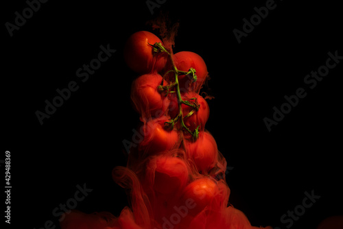 Red tomatoes on a twig with red liquid on black background #429488369