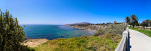 A Panoramic Shot Of The Coast With Vast Deep Blue Ocean Water And Waves Crashing Into The Beach With Blue Sky And Lush Green Trees And Plants On The Hillside At Point Fermin Park In San Pedro CA