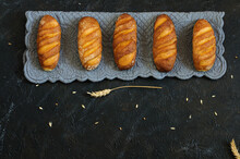 Horizontal Row Of Small Loaves On A Gray Napkin, Against A Black Background With Copy Space Below