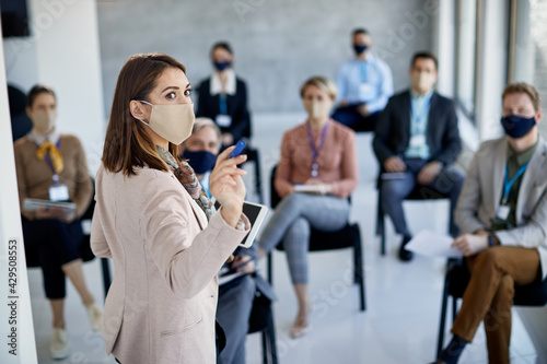 Obraz Businesswoman wearing protective face mask while giving presentation in board room. - fototapety do salonu