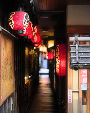Selective Focus On The First Of A Line Of Red Paper Lanterns Leading Into A Dimly Lit Covered Alley In Central Osaka