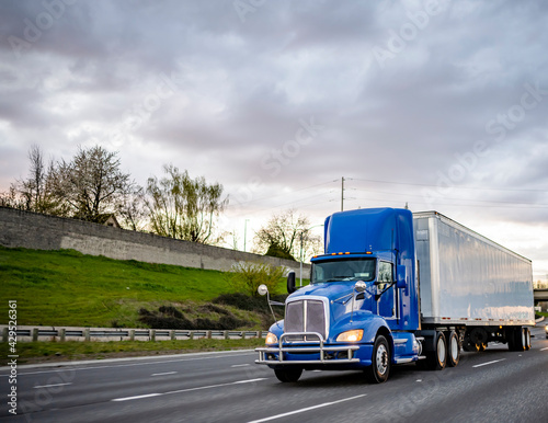 Fotografia Blue big rig day cab industrial semi truck with turn on headlight transporting c