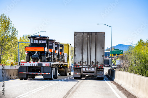 Two loaded big rig semi trucks with different semi trailers running side by side on the narrow two line highway intersection at sunny day - fototapety na wymiar