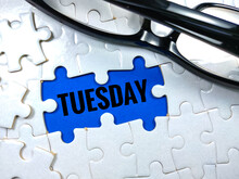 Selective Focus.Word TUESDAY With Glasses And Jigsaw Puzzle On Blue Background.Business Concept.