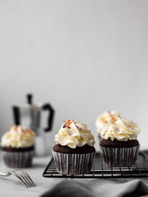 Chocolate Cupcakes On A Black Metal Grill On A Light Background With A Coffee Pot