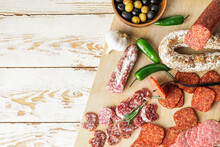 Board With Slices Of Different Sausages On Wooden Background