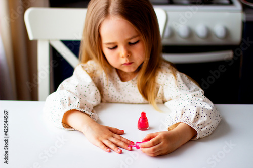 Little girl paints her nails with pink nail polish Fototapeta
