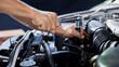 A car mechanic is doing a car repair in a repair shop.