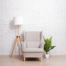 Armchair, Lamp And Plant Over Brick Wall