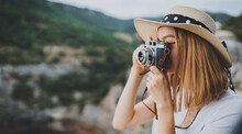 Young Blonde Girl In Summer Hat Takes Photo On Retro Camera On Background Panorama Horizin Mountain Landscape, Hipster Tourist Enjoys Hobby Of Photographer  Leisure In Summer Nature Empty Space