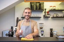 Joyful Young Bearded Man Wiping Bar Counter