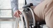 Close up of disabled man riding in wheelchair