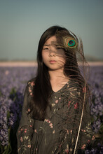 Girl In Field Of Flowers With A Peacock Feather Hiding One Eye