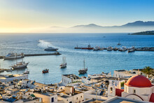 Beautiful View Of Chora, Mykonos, Greece At Sunset. Port, Bay, Boats, Yachts Moored By Jetty. Famous Whitewashed Houses, White Church With Red Dome