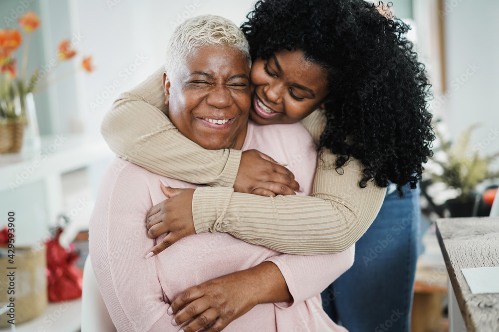 Fotografia African daughter hugging her mum indoors at home - Mother day concept - Main foc
