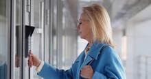 Mature Woman Scanning Fingerprint On Alarm System Entering Business Center