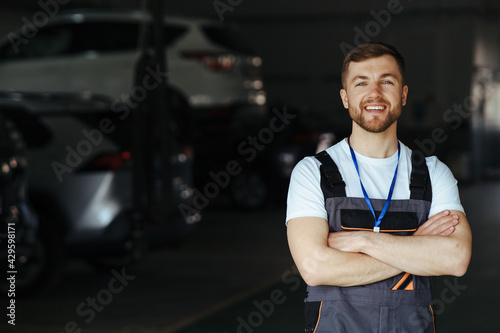 Papel de parede Auto mechanic standing in his workshop in front of a car