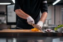 Close Up Of Chef Cook Hands In Gloves Cutting Or Chop Yellow Pepper At Kitchen