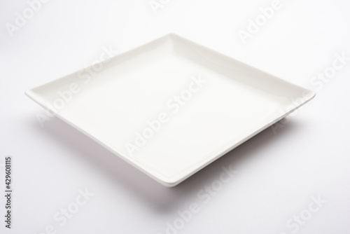 Obraz na plátně Empty white ceramic square plate isolated on white